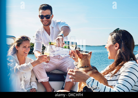 Man pouring champagne for young women on boat, Gavle, Sweden - Stock Photo