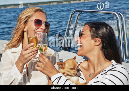 Two young women on boat toasting wine - Stock Photo