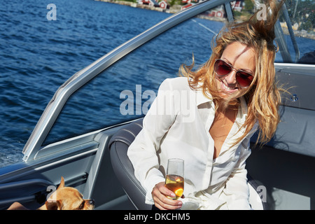 Young woman on boat with glass of wine - Stock Photo