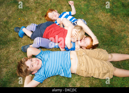 Three brothers and sister lying on grass in garden - Stock Photo
