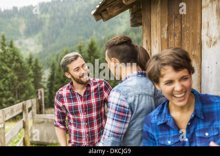 Group of friends chatting behind wooden shack - Stock Photo