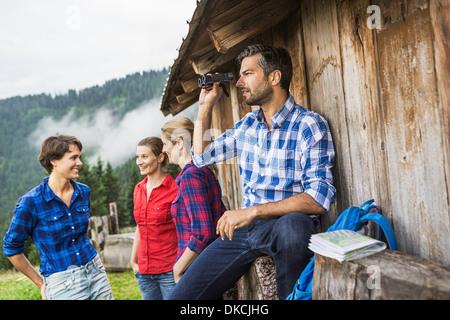 Friends chatting enjoying view through binoculars, Tirol, Austria - Stock Photo