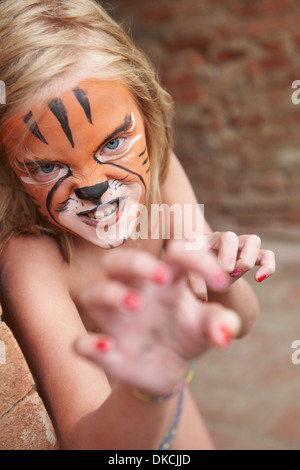 Girl with face painting imitating tiger - Stock Photo