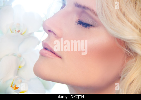 Close up of woman smelling orchids - Stock Photo
