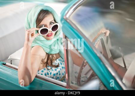 Woman in headscarf lowering sunglasses in vintage convertible - Stock Photo