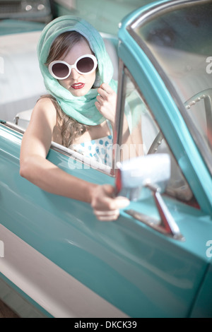 Woman in headscarf and white sunglasses in vintage convertible - Stock Photo