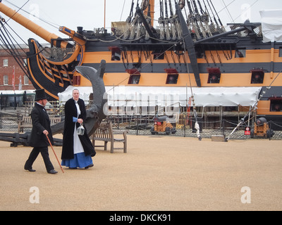 Actors in Victorian costume walk past HMS Victory in Portsmouth Historic Dockyard, England - Stock Photo