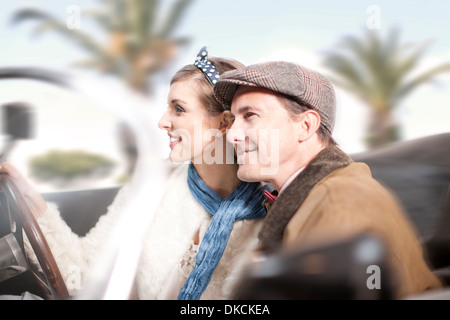 Side view of couple in convertible - Stock Photo