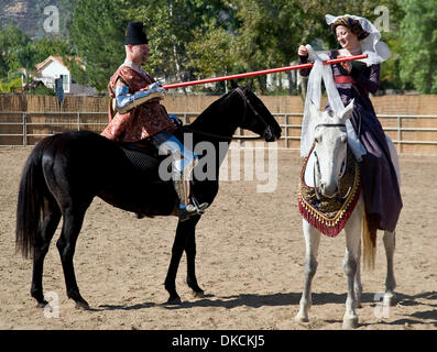 Oct. 23, 2011 - Poway, California, USA -  A fair lady ties her ribbon onto a lance prior to a mounted battle melee - Stock Photo