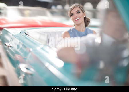 Woman enjoying ride in back seat of vintage convertible - Stock Photo