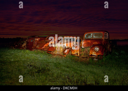 Vintage cars abandoned in scrap yard - Stock Photo