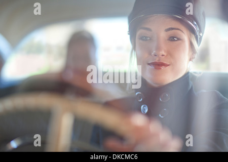 Woman playing chauffeur in vintage car - Stock Photo