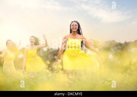 Girls in yellow dancing on meadow - Stock Photo