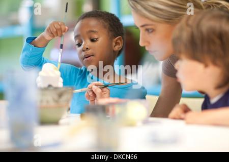 Teacher and children in art class - Stock Photo