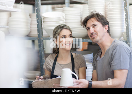 Potters chatting at crockery factory - Stock Photo