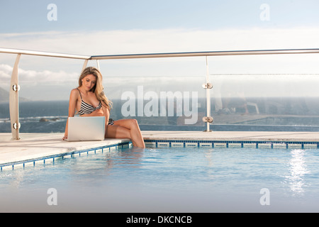 Woman using laptop by swimming pool, Cape Town, South Africa - Stock Photo