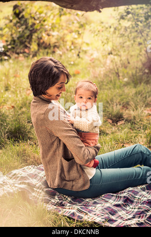 Mother and baby enjoying park - Stock Photo