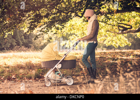 Mother walking baby in pram in forest - Stock Photo