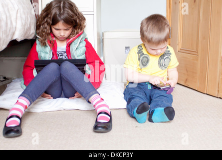 Children using digital tablet and cellular phone - Stock Photo
