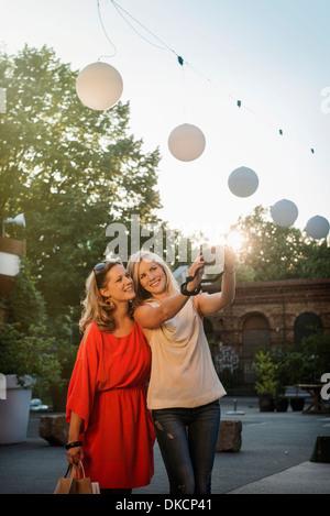 Two women taking self portrait, Berlin, Germany - Stock Photo