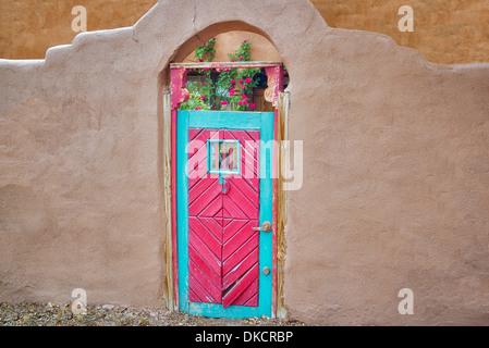 Red Historic door and adobe building near Santa Fe, New Mexico. - Stock Photo