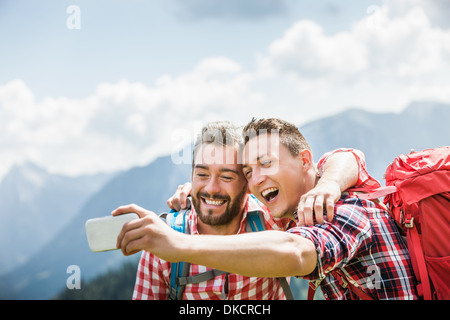 Two male friends photographing themselves, Tyrol, Austria - Stock Photo