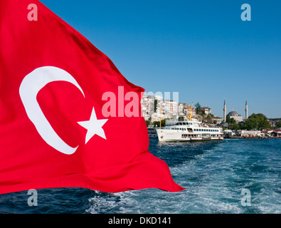 A Turkish flag on the back of a boat crossing the Bosphorus in Istanbul Turkey - Stock Photo