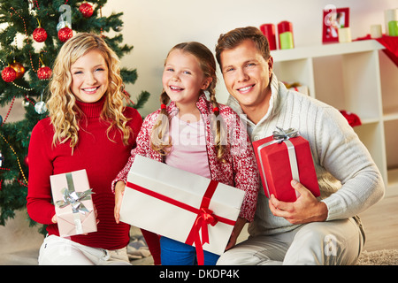 Portrait of happy family with giftboxes looking at camera on Christmas day - Stock Photo