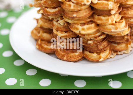 Many waffles stacked on white plate, on top of green dotted table cloth - Stock Photo