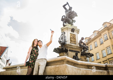 Young couple taking self portrait photograph beside statue in Augsburg, Bavaria, Germany - Stock Photo
