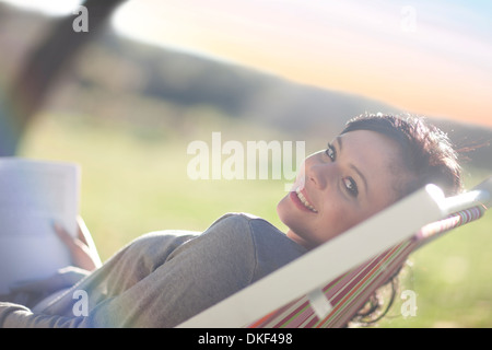 Young woman reclining in deck chair with book - Stock Photo