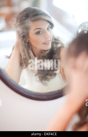 Young woman checking herself in wall mirror - Stock Photo