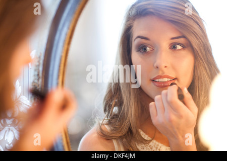 Young woman applying lipstick in mirror - Stock Photo