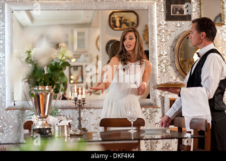 Young woman and butler in dining room - Stock Photo