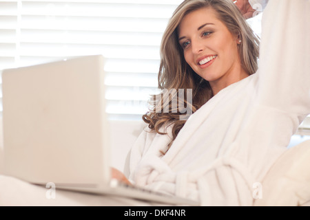 Young woman lying in bed with laptop - Stock Photo