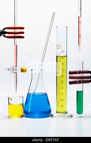 Chemical lab glassware: burette over beaker, Erlenmeyer flask with stirring rod, graduated cylinder, pipette over - Stock Photo