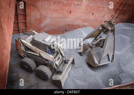 High angle view of digger and grab unloading metal alloy in ship's hull - Stock Photo