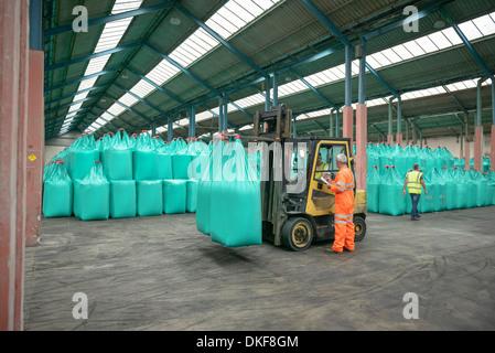 Workers and fork lift truck in bulk fertiliser store in port - Stock Photo