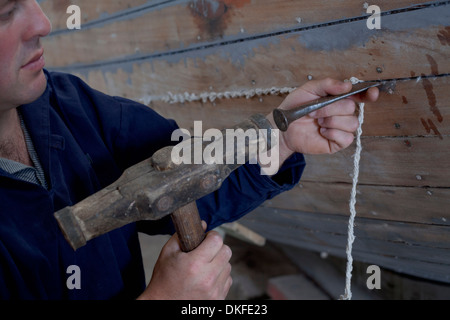 Man hammering string into boat in workshop - Stock Photo