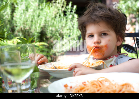 Portrait of messy male toddler eating spaghetti - Stock Photo
