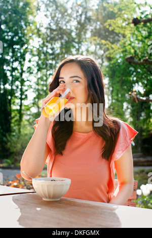 Portrait of young woman drinking orange juice in garden - Stock Photo