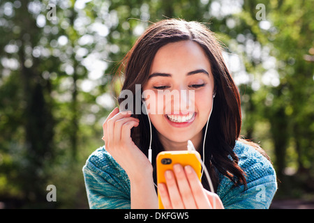 Portrait of young woman listening to music - Stock Photo