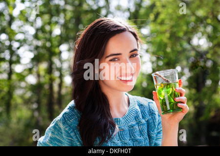 Portrait of young woman in garden with soft drink