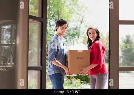 Couple moving house woman carrying pot plant man carrying lamp stock photo royalty free image - Young couple modern homes ...