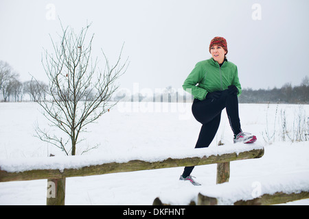 Female jogger stretching before run in snow covered scene - Stock Photo