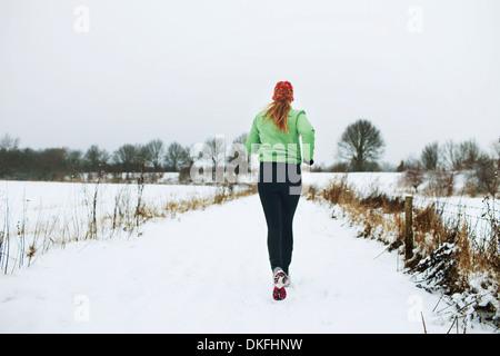 Female jogger running in snow - Stock Photo