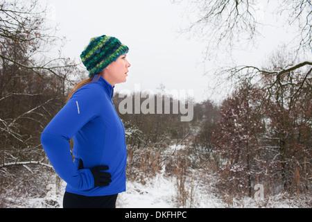 Female runner taking a break in winter scene - Stock Photo