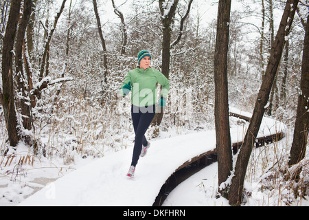 Female running on elevated forest walkway in winter - Stock Photo