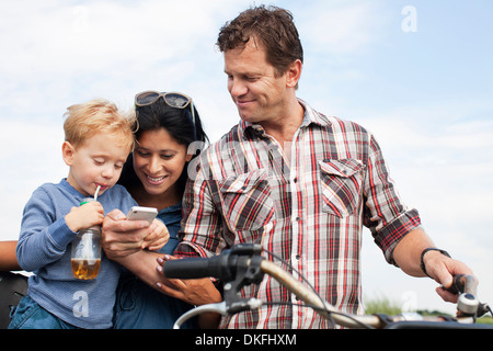 Family looking at smartphone and having a drink - Stock Photo