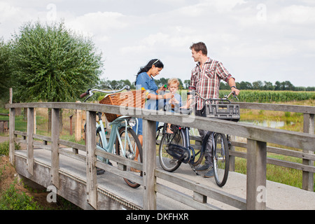 Family on bicycles on wood bridge, stopped for drink - Stock Photo